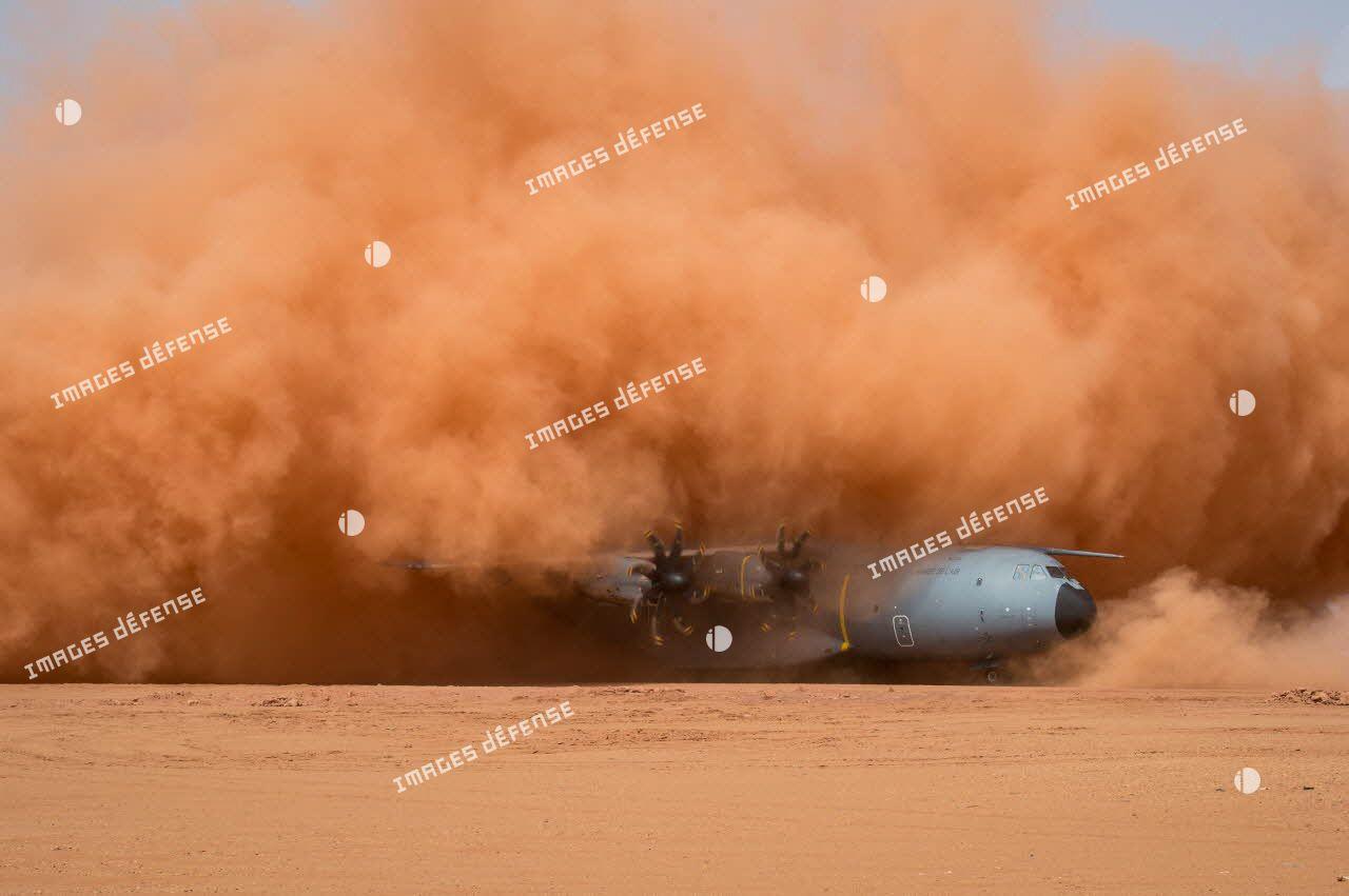 Atterrissage d'expérimentation d'un avion A400M sur la piste de Madama, dans un nuage de poussière ocre.