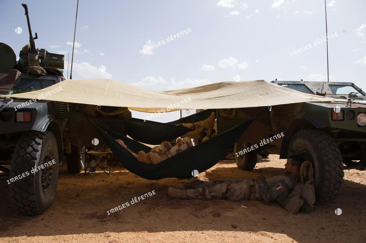 Des soldats d'une patrouille franco-nigérienne se reposent sur des hamacs tendus entre deux véhicules blindés légers (VBL) dans le désert nigérien.