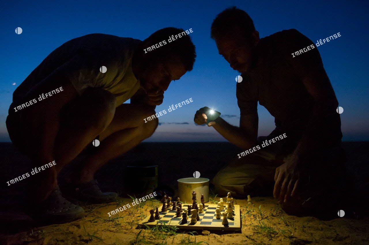 Des éléments du détachement de liaison et d'appui opérationnel n°3 (DLAO 3) disputent une partie d'échecs nocturne dans le désert malien.