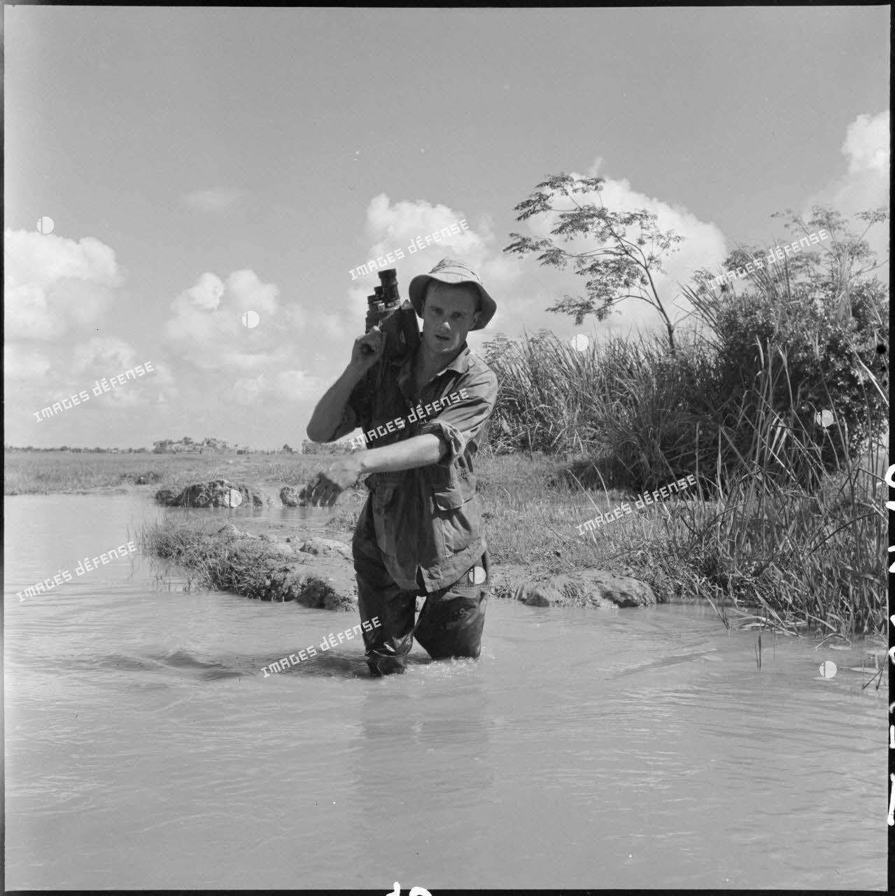Le cinéaste Pierre Schoendoerffer progresse dans une rizière avec une caméra Bell&Howell sur l'épaule au cours de l'opération Claude dans le secteur de Tien Lang.