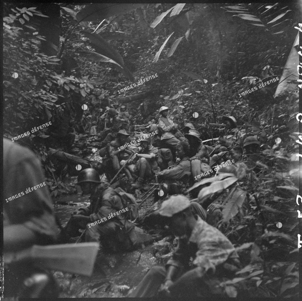 Des parachutistes de la colonne Langlais font une halte au bord d'un ruisseau en plein jungle, au cours de leur progression vers le Laos.