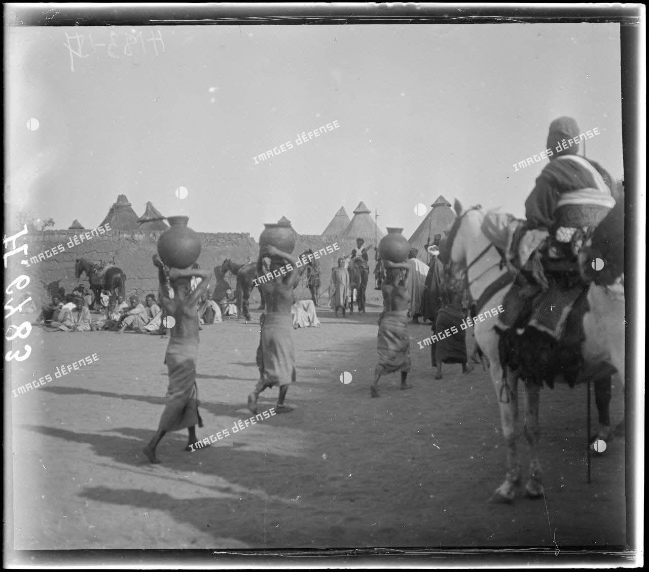 N'Gaoundéré village. Femmes portant de l'eau pour le sultan. [légende d'origine]