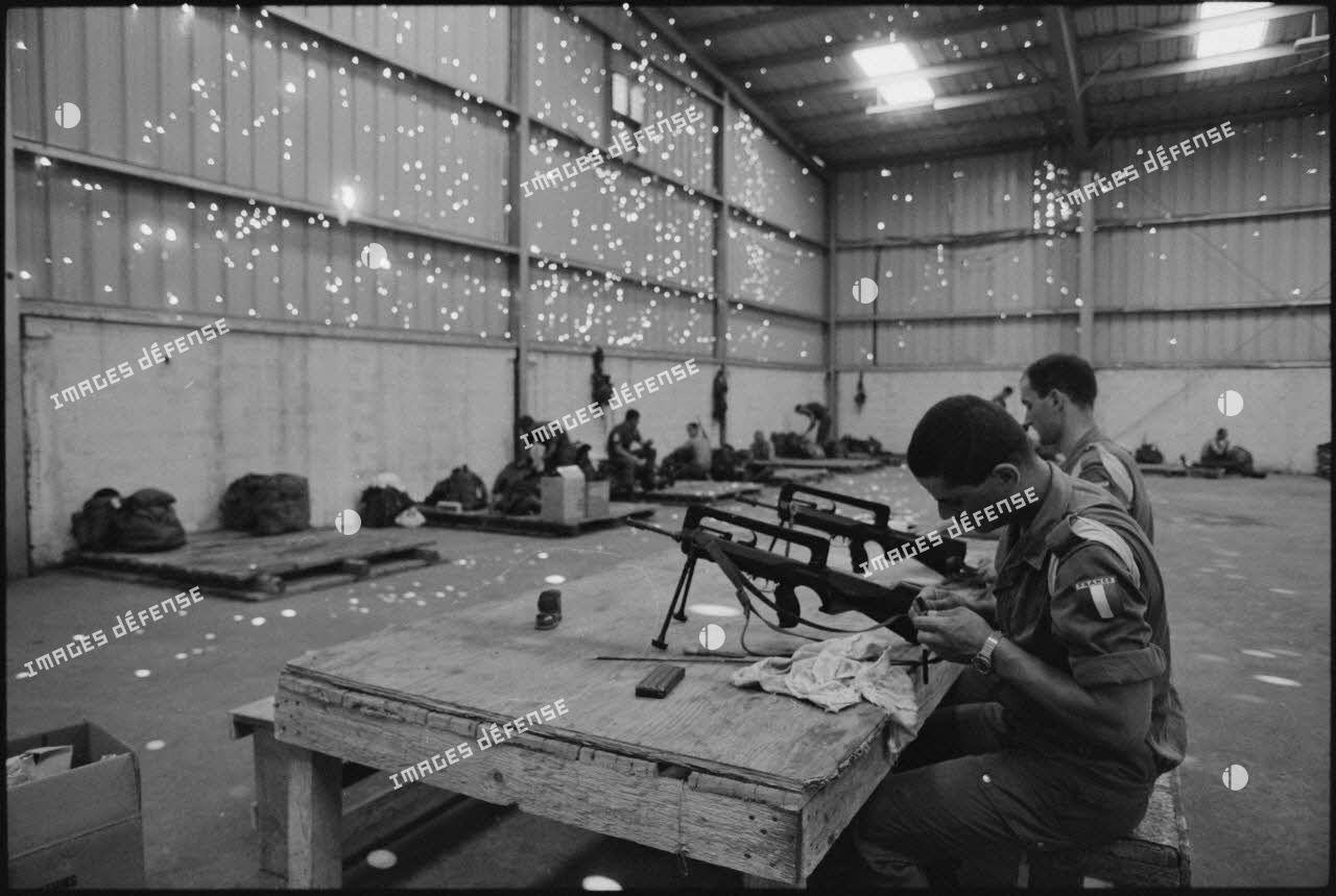 Légionnaires du 2e régiment étranger de parachutistes (REP) nettoyant leurs fusils d'assaut de la manufacture d'armes de Saint-Etienne (FAMAS).