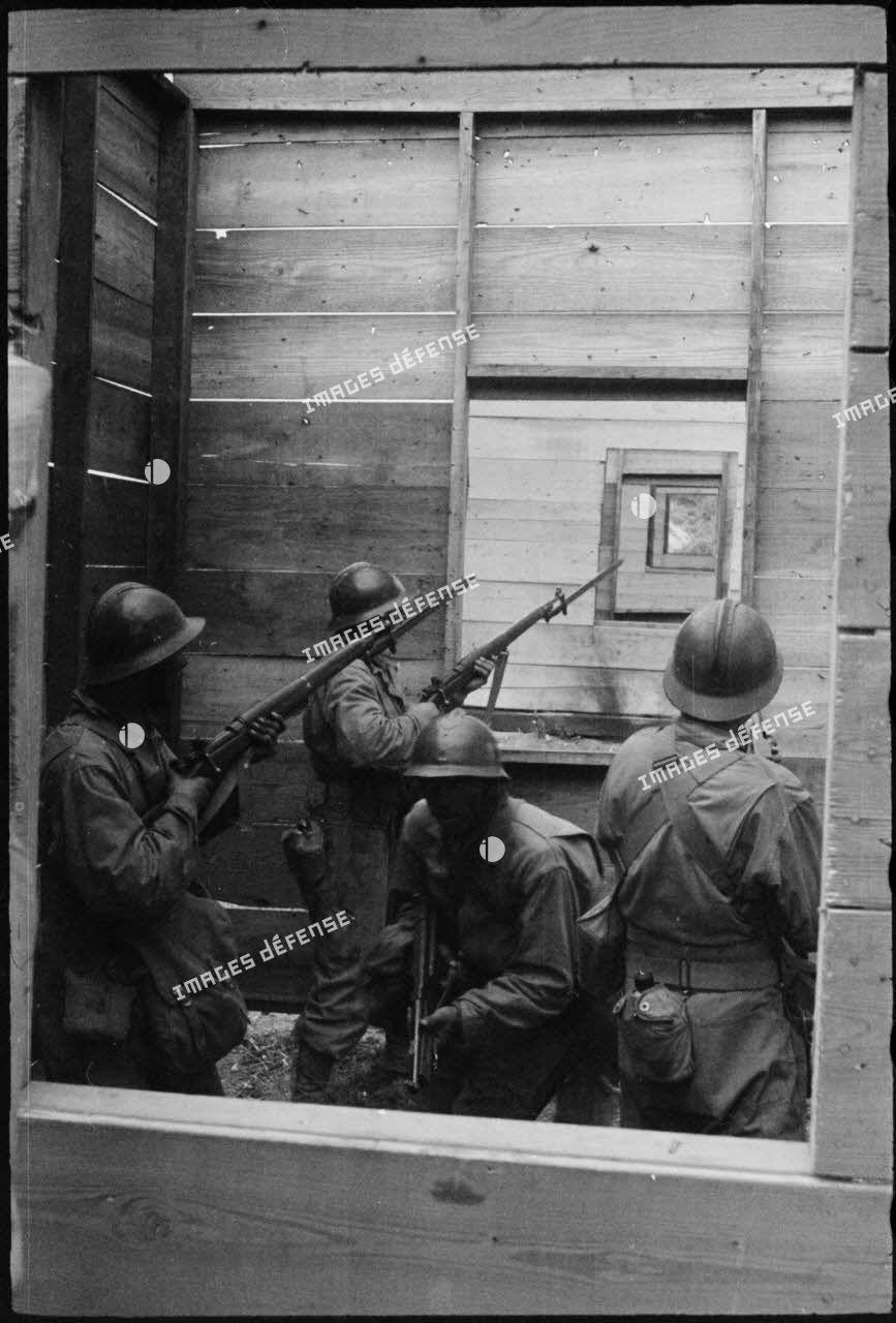 Entraînement au combat urbain dans un camp en Algérie: des soldats français occupent une maison factice.