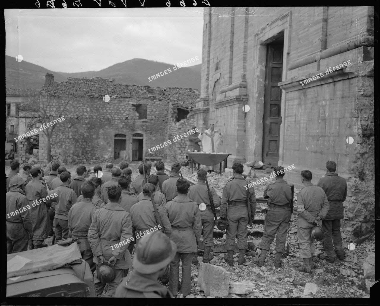 Des tirailleurs du 5e régiment de tirailleurs marocains (RTM) de la 2e division d'infanterie marocaine (DIM) assistent à la messe de Noël, célébrée par un aumônier militaire catholique sur le parvis de l'église d'un village situé à proximité des premières lignes italiennes.