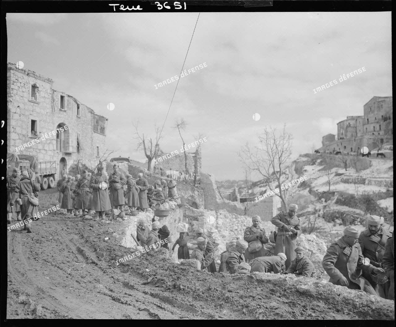 Des tirailleurs du 6e régiment de tirailleurs marocains (RTM) de la 4e division marocaine de montagne (DMM) se restaurent à l'entrée du village de Viticuso (à douze kilomètres à l'est de Cassino) avant d'être mis à la disposition de la 3e division d'infanterie algérienne (DIA).