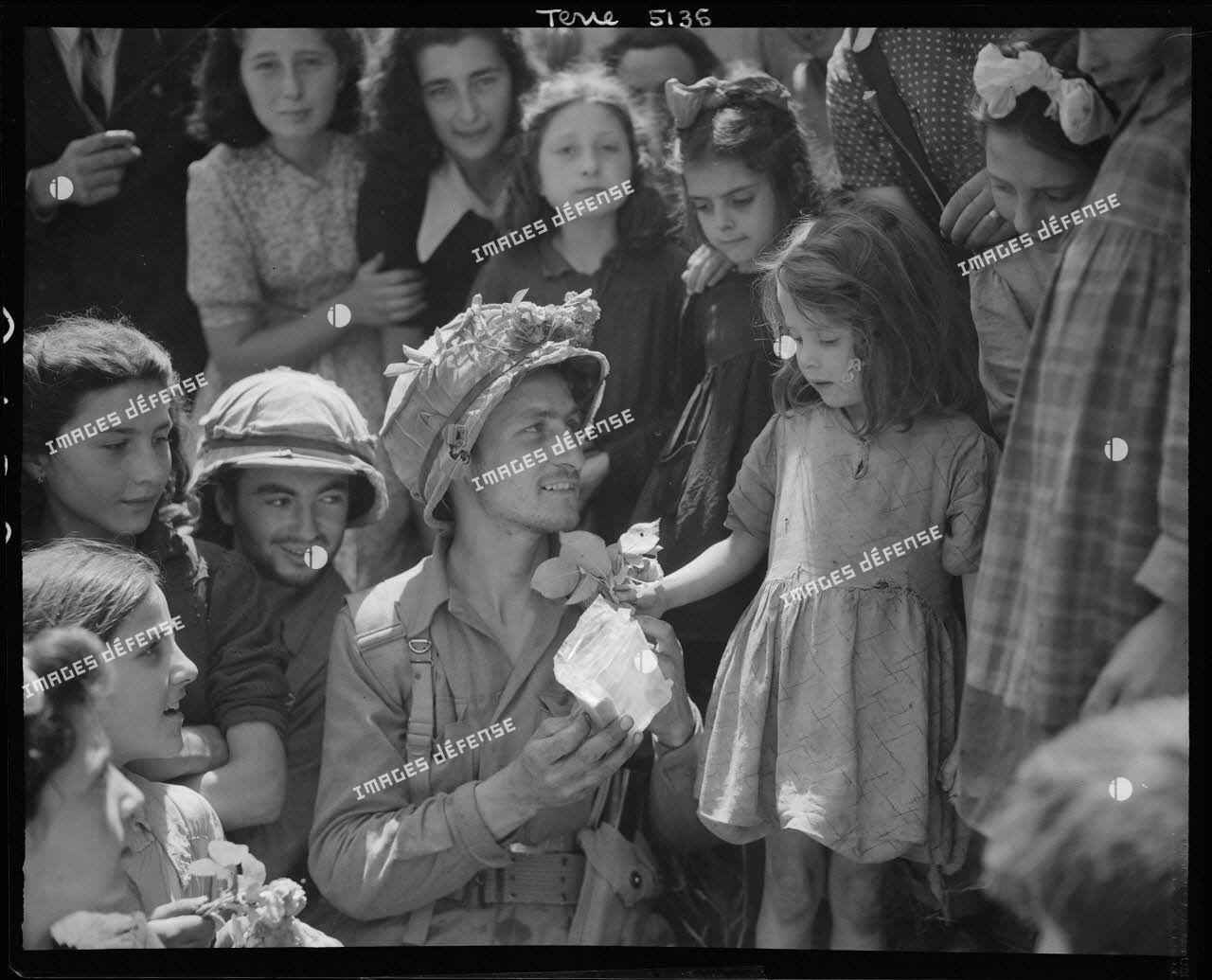 À Colleferro, à quarante kilomètres au sud-est de Rome, une enfant offre des fleurs à un soldat de la 1st special service force (détachement du service spécial) de la 5e armée américaine.