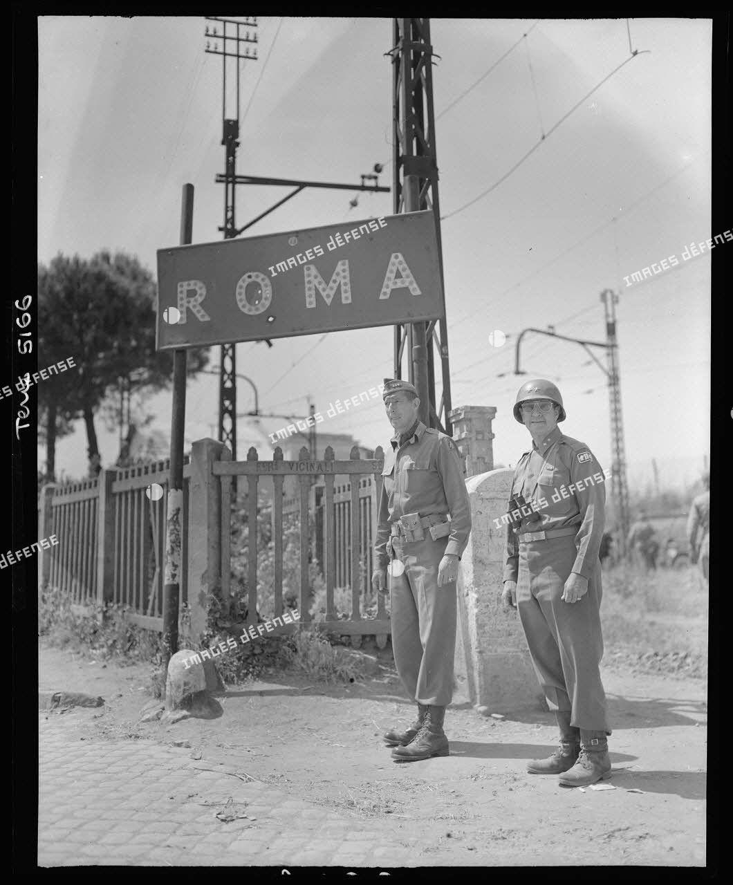 Le lieutenant general Mark Wayne Clark, commandant la 5e armée américaine, pose symboliquement devant un panneau indicateur aux portes de Rome libérée ; à ses côtés, l'un de ses grands subordonnés, le major general Geoffrey Keyes, commandant le 2e corps d'armée.