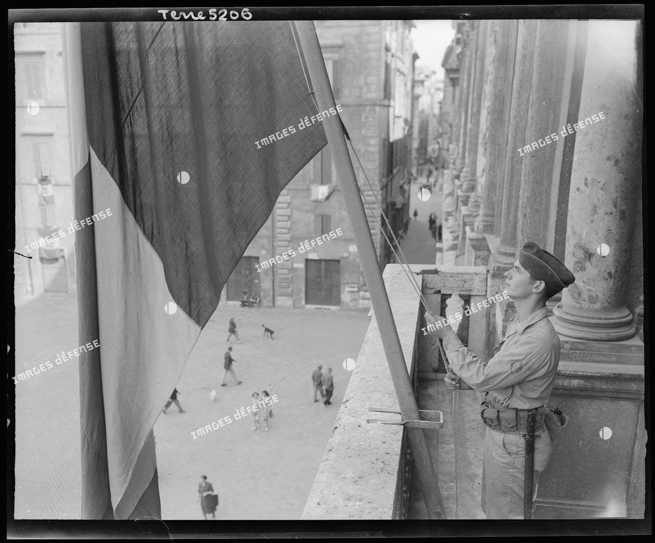 Le marsouin Paul Poggionovo, du bataillon d'infanterie de marine et du Pacifique (BIMP) de la 1re division de marche d'infanterie (DMI), ex.1re division française libre (DFL), hisse symboliquement le drapeau français sur le palais Farnese, siège de l'ambassade de France à Rome.