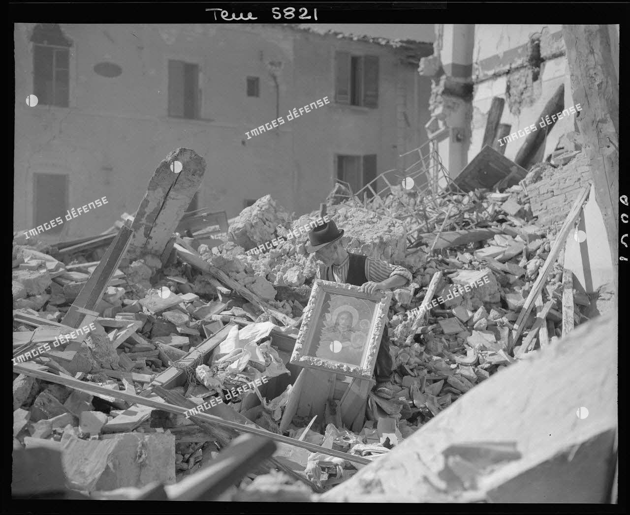 Civil italien fouillant les ruines de sa maison.