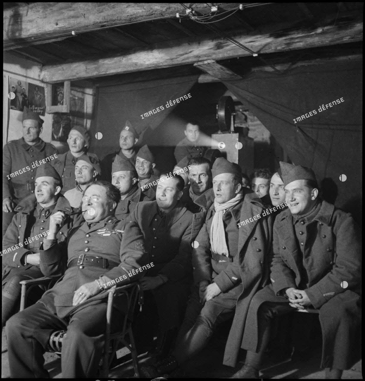 Photographie de groupe de soldats de différentes unités de la 2e armée qui assistent à une séance de cinéma aux armées.