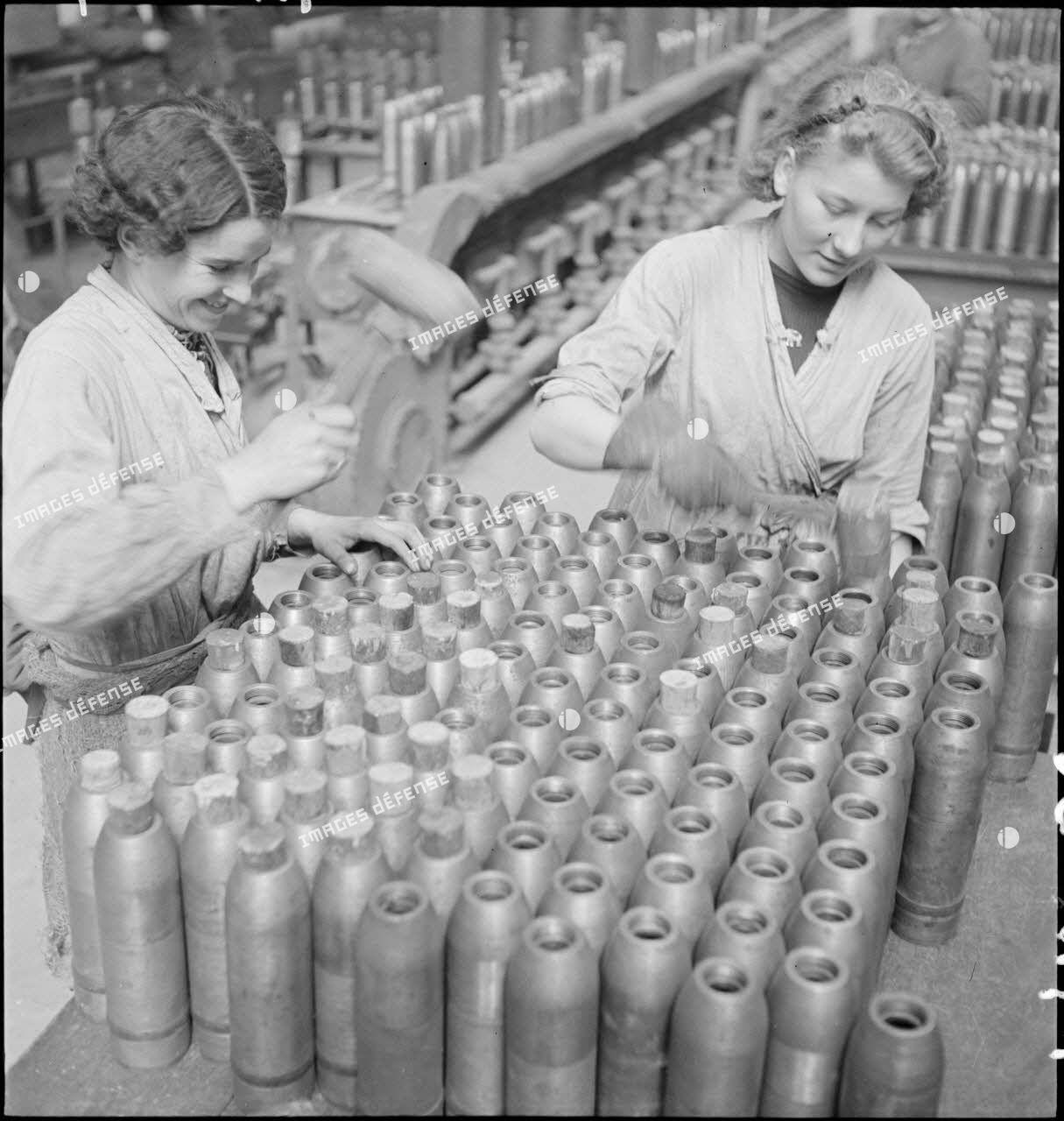 Dans une cartoucherie ou un atelier de fabrication, des ouvrières ferment des enveloppes d'obus de 75 mm avec des bouchons de bois.