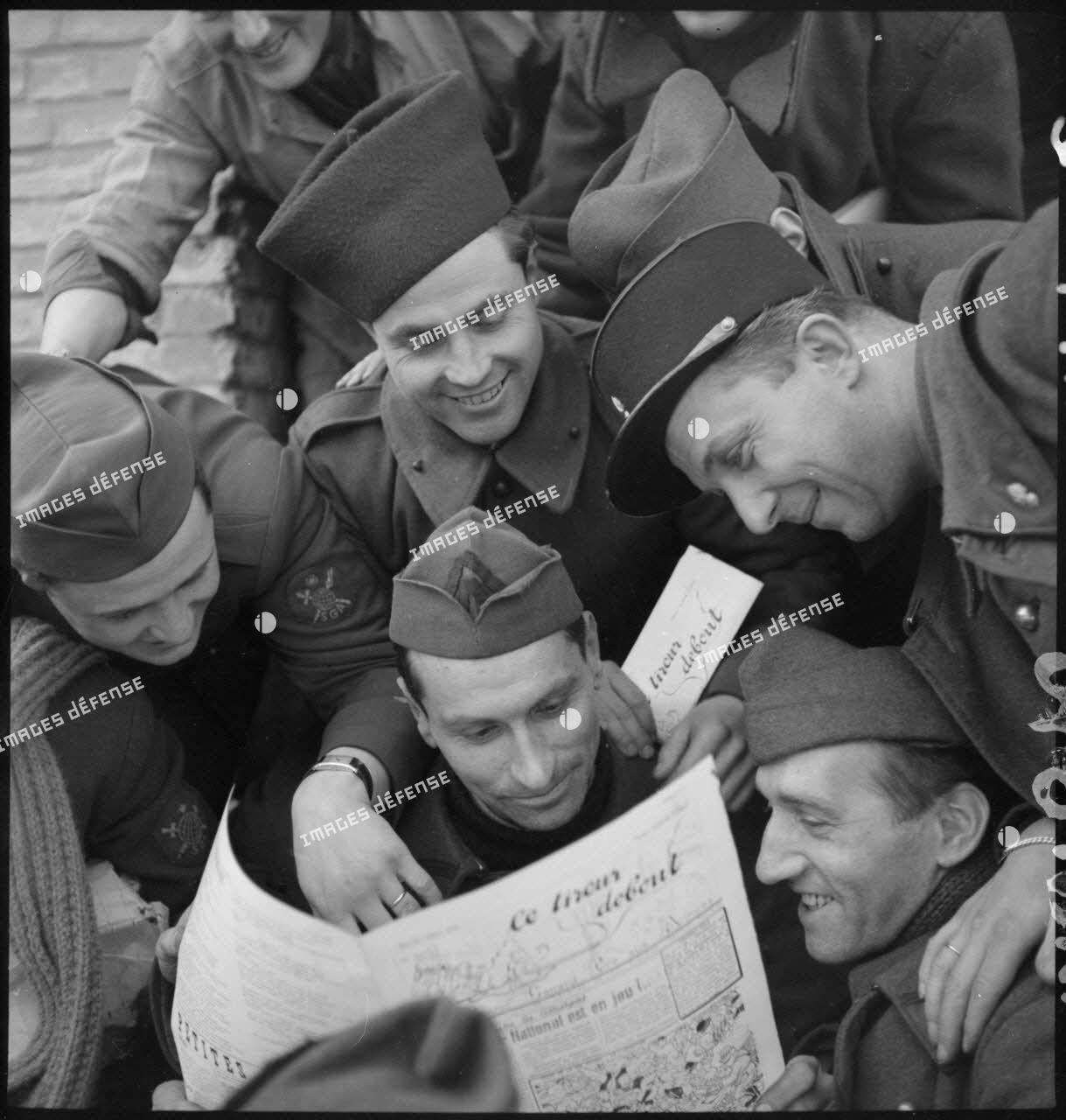 Des soldats de diverses unités (spahis, service géographique des armées...) lisent un numéro du journal de campagne intitulé Le tireur debout.
