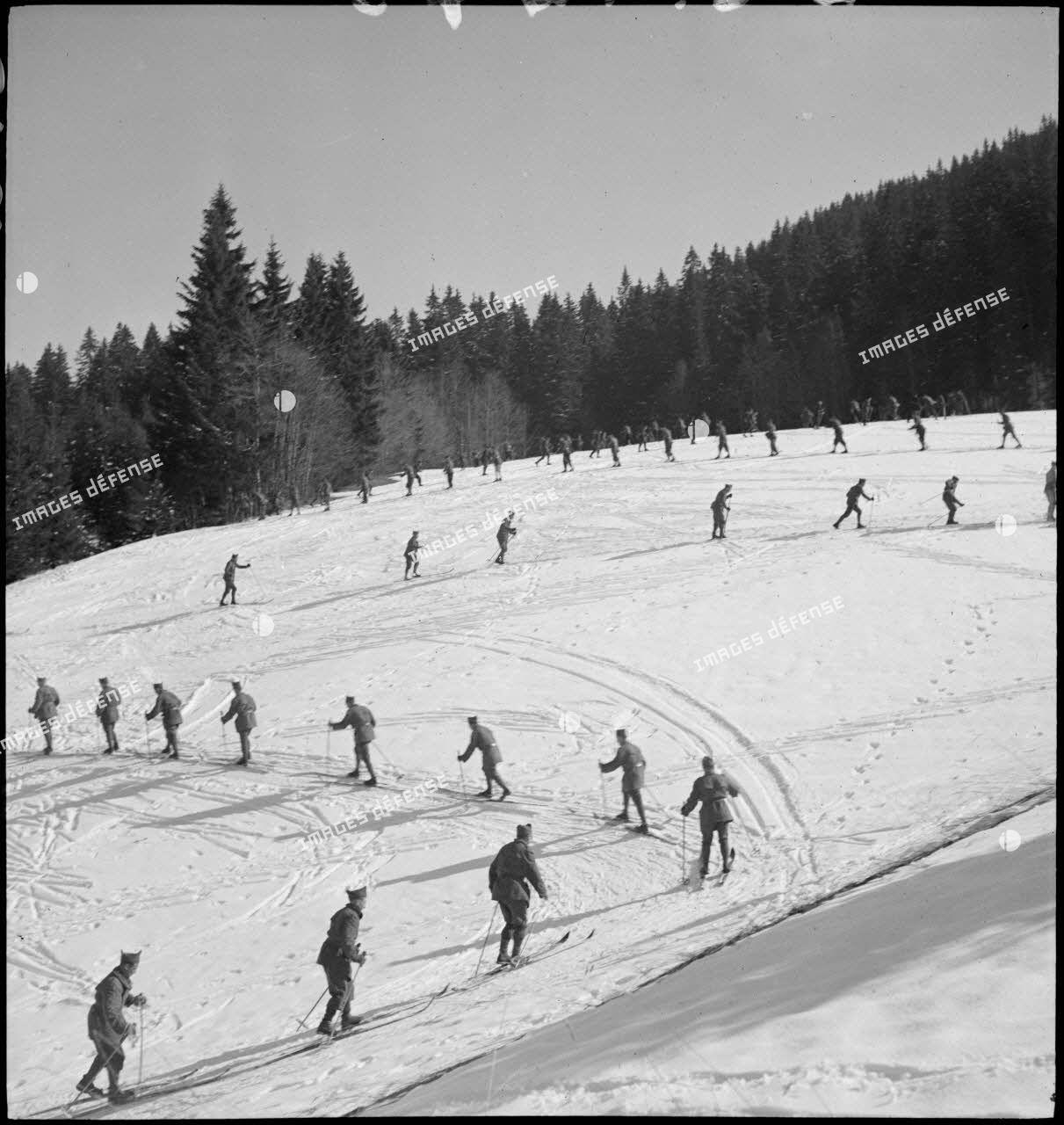 Plan général de chasseurs alpins qui se déplacent à ski le long d'une pente enneigée.
