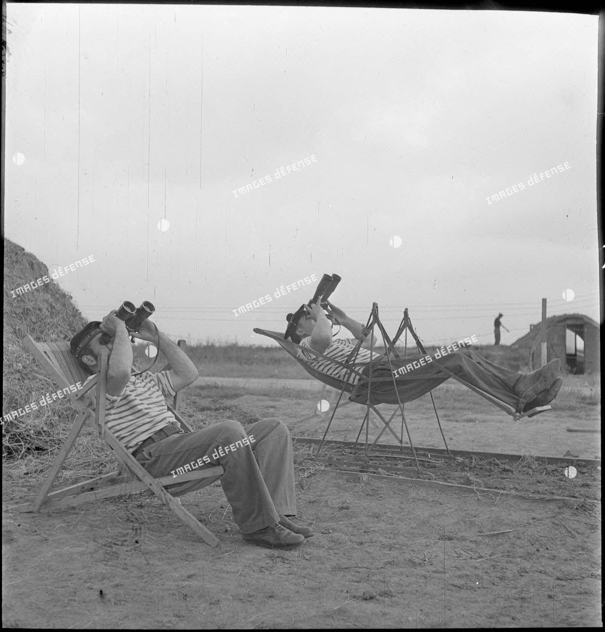Des marins, appartenant à la 4e batterie de 90 mm contre avions, batterie mobile de défense antiaérienne de la Marine, observent le ciel à l'aide de jumelles, installés dans des chaises longues ou des sièges suspendus.