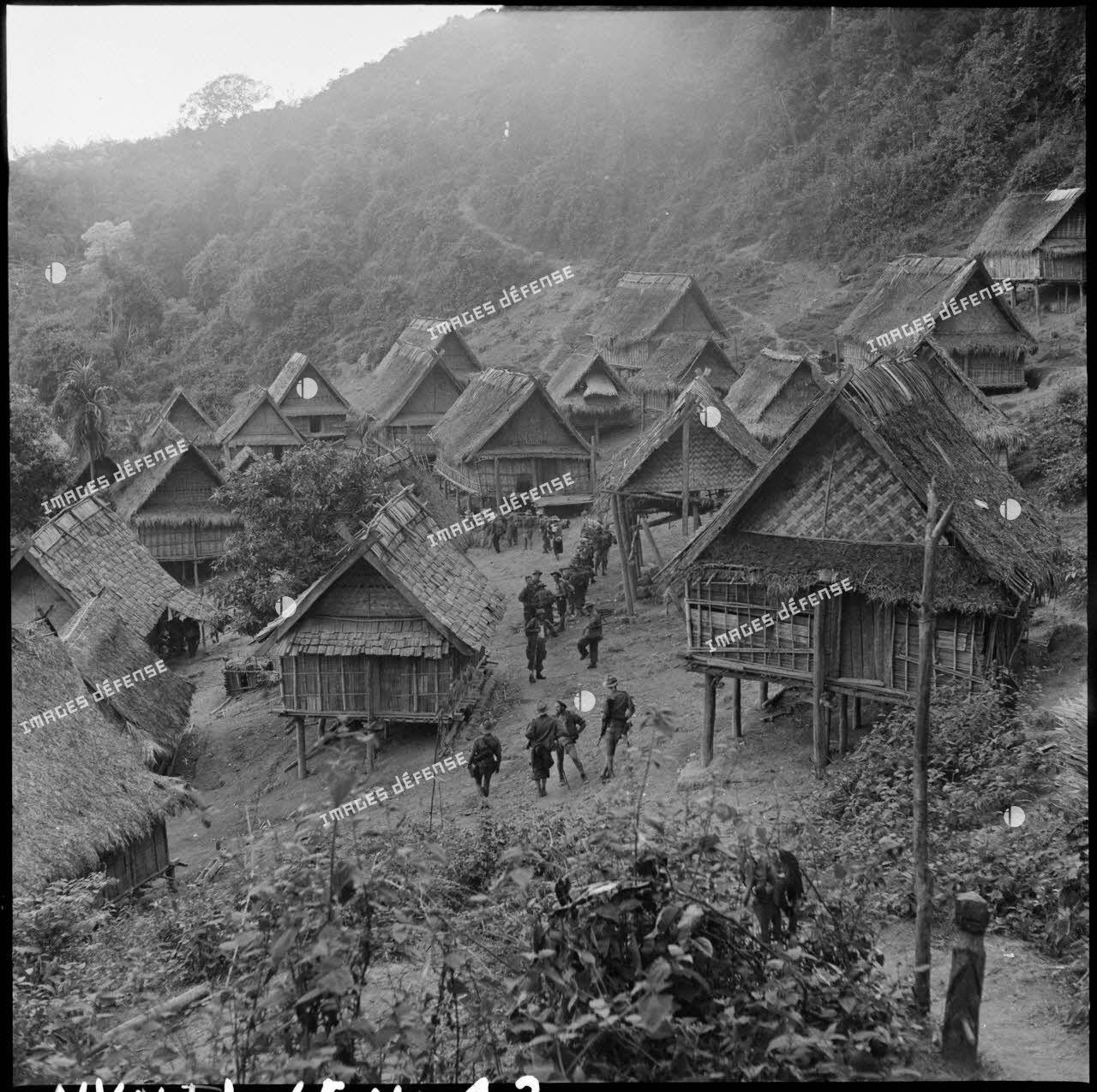 Des soldats de la colonne Godard traversent le village de Phu Teng lors de l'opération Condor.