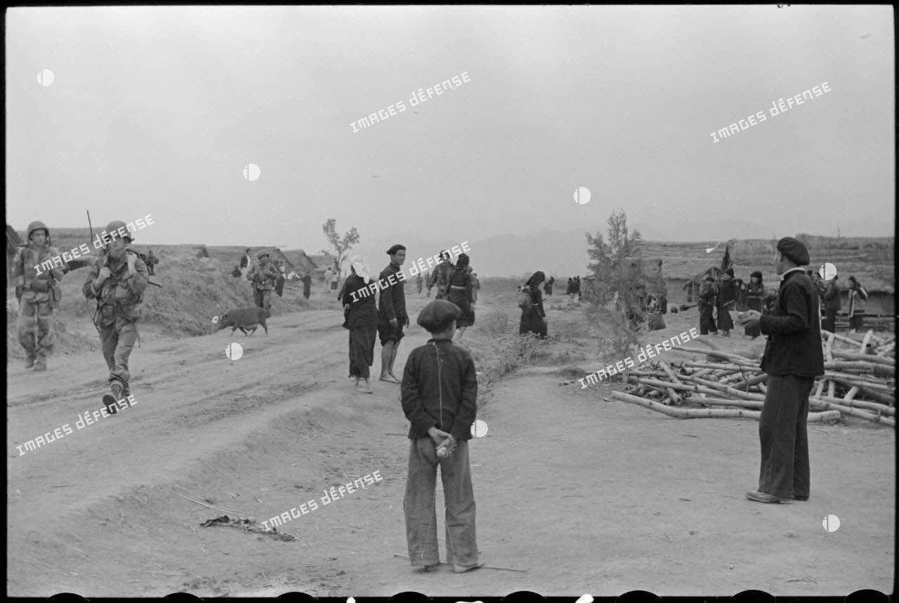 Des troupes parachutées près du camp de Diên Biên Phu traversent un village habité par des Thaï.