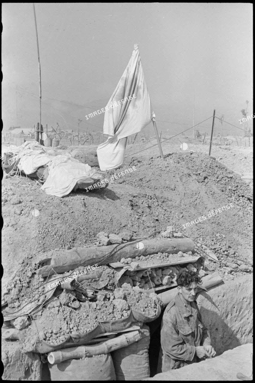 Soldat dans une tranchée à l'entrée d'une antenne chirurgicale du camp retranché de Diên Biên Phu, sur laquelle flotte le drapeau blanc à Croix-rouge.