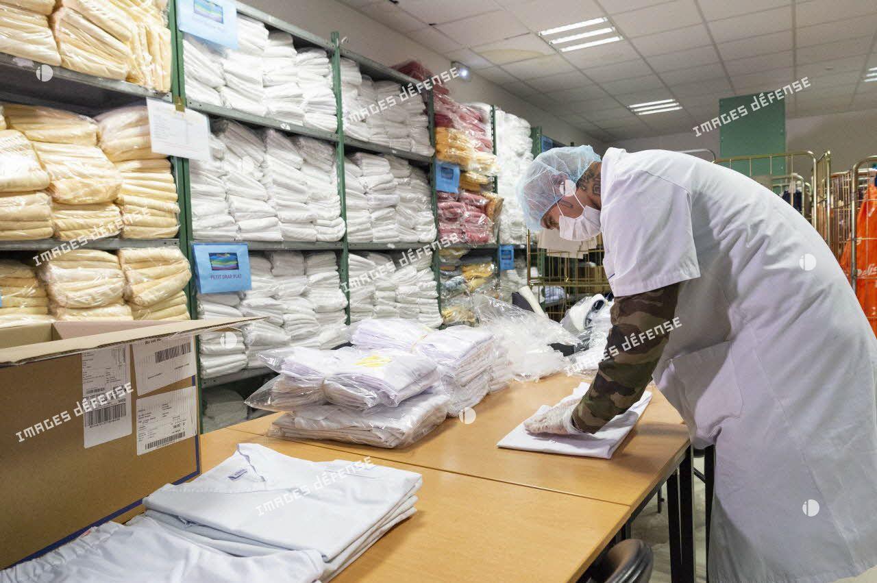 Un soldat apporte son aide pour le pliage du linge médical à l'hôpital Sainte-Anne.