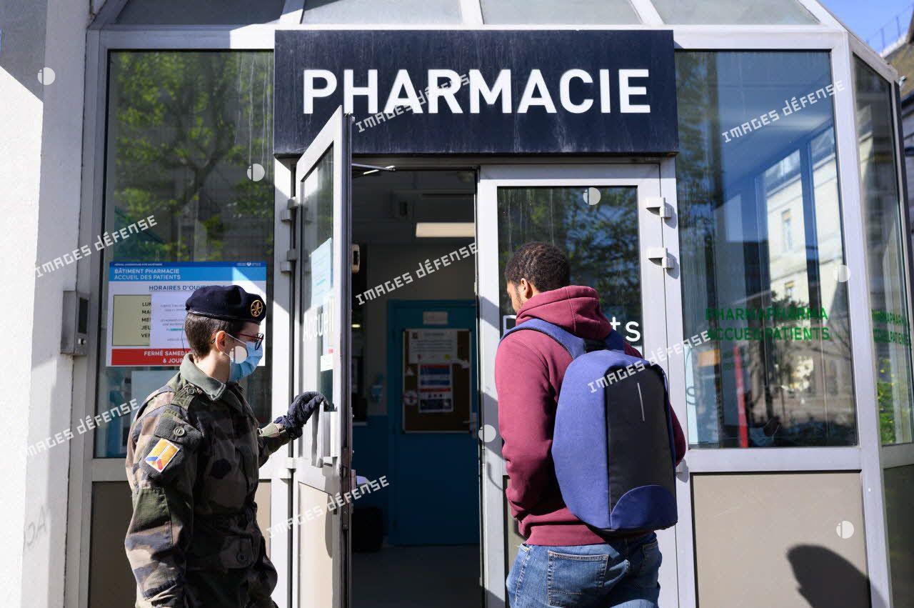 Un soldat du 24e régiment d'infanterie (24e RI) ouvre la porte à un patient à l'entrée de la pharmacie de l'hôpital de la Pitié Salpêtrière à Paris.