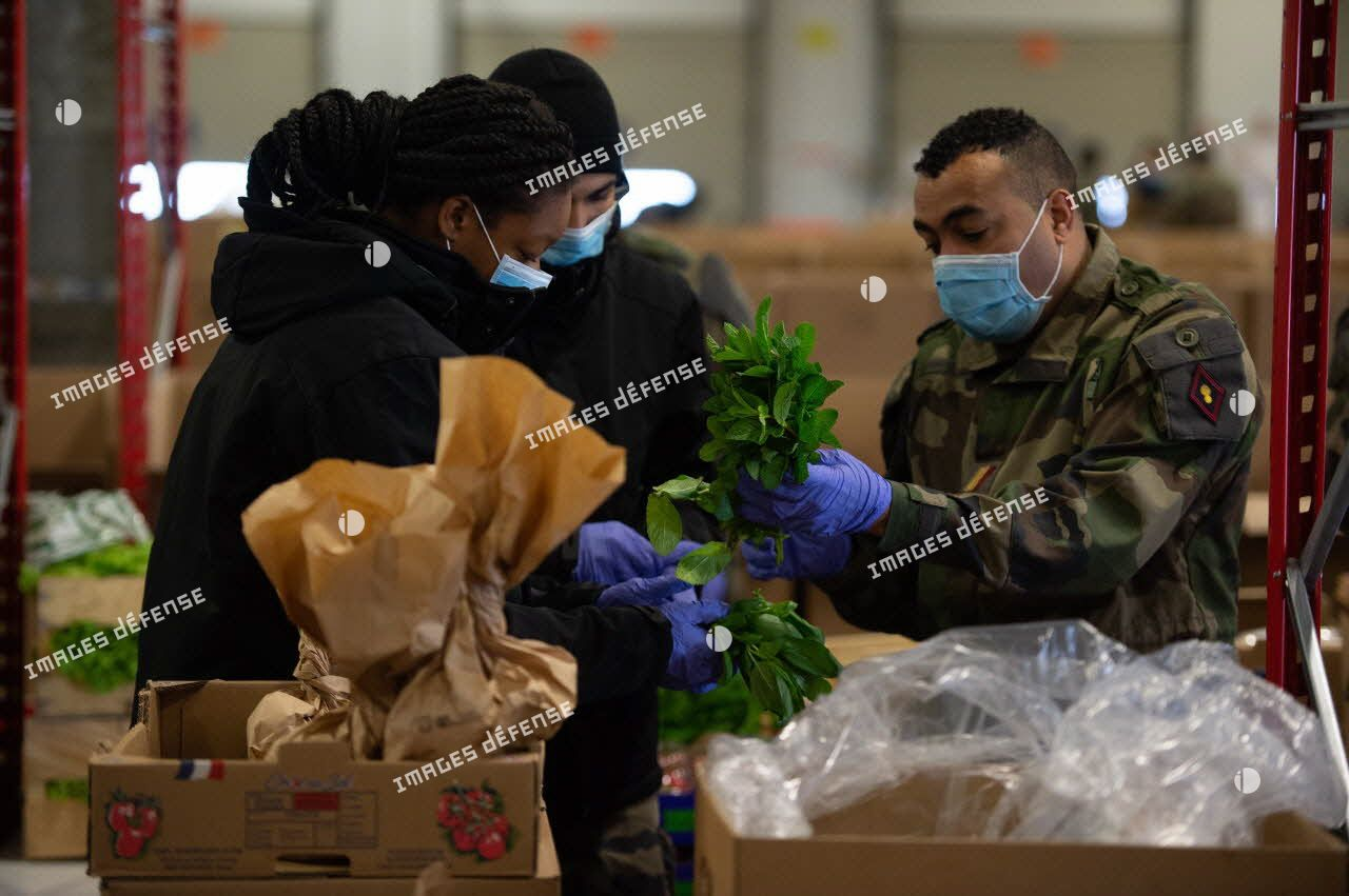 Des éléments du 2e régiment du service militaire volontaire (2e RSMV) préparent des colis de livraison alimentaires au sein d'un entrepôt du marché d'intérêt national de Rungis.