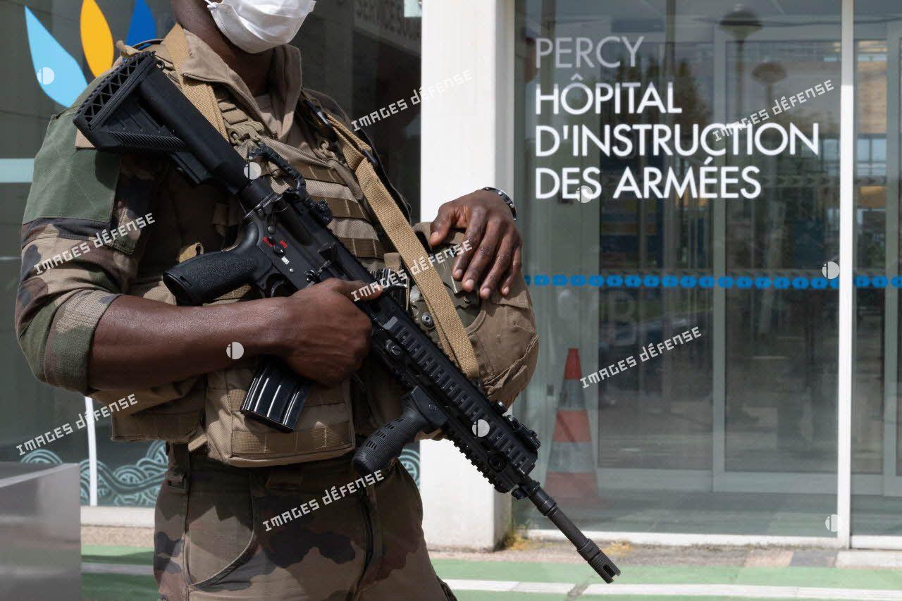 Un élément du 2e régiment du service militaire volontaire (2e RSMV) patrouille devant l'entrée de l'hôpital d'instruction des armées (HIA) Percy, à Clamart.