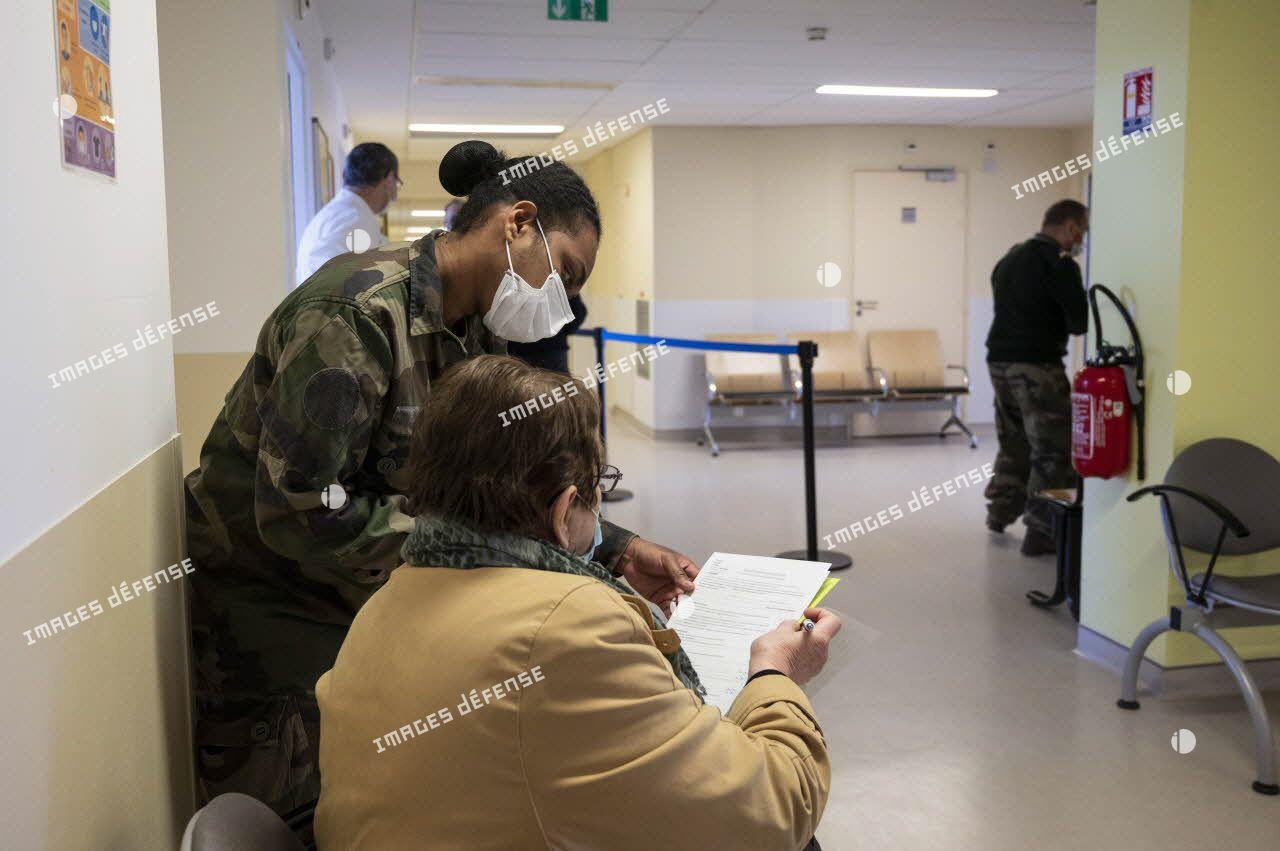 Un militaire aide une patiente à remplir son formulaire de vaccination au sein de l'hôpital d'instruction des armées (HIA) Bégin.
