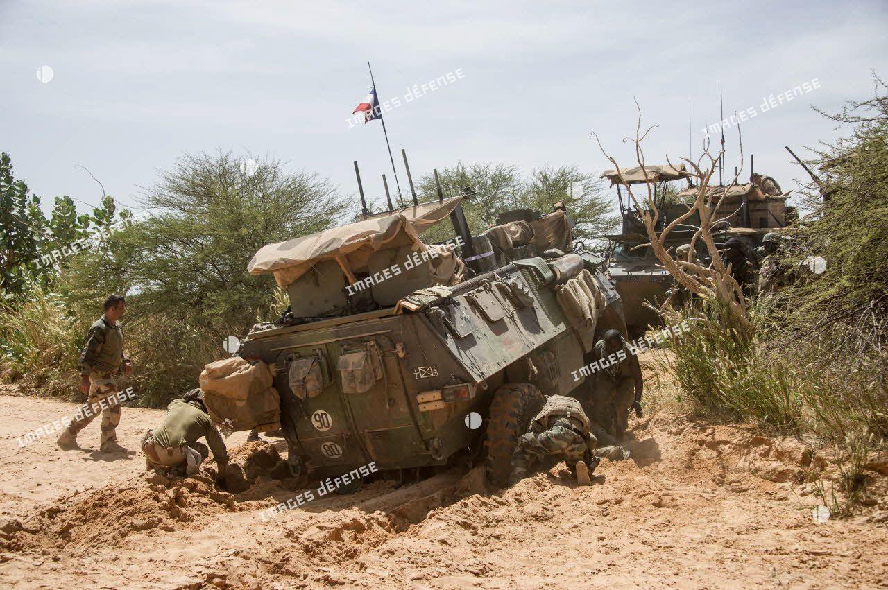 Des soldats des forces armées maliennes (FAMa) dégagent un véhicule de l'avant blindé (VAB) ensablé dans un oued lors du franchissement du fleuve Niger.