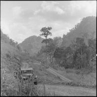 Progression lente d'un convoi militaire sur une route en lacets du pays Thaï.