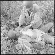 Un soldat blessé lors d'un accrochage sur la RP 41 (route provinciale 41) en pays Thaï se fait poser un pansement à même le sol.