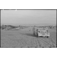 A bord d'un cabriolet Auto-Union, un capitaine (peut-être l'Hauptmann Joseph Karl) Gruppenkommandeure III./LLG.1 inspecte l'aérodrome de Valence-Chabeuil (Drôme) avant une mission.