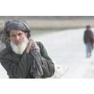 Portrait d'un vieil Afghan passant au pied des remparts de la citadelle de Quala i Jangi près de Mazar e Charif.