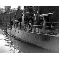 [Marine : canonnière, déchargement de cargo, usine, côte vue d'un canot.]