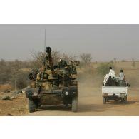 Déploiement de l'opération de la force européenne EUFOR Tchad/RCA (République centrafricaine) : un véhicule blindé léger ERC-90 Sagaie, élément d'un détachement du bataillon Centre en patrouille à proximité du camp de Forchana, croise un véhicule civil tchadien.