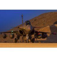 Un avion Rafale se tient prêt au décollage sur la piste de la base aérienne projetée (BAP) en Jordanie.