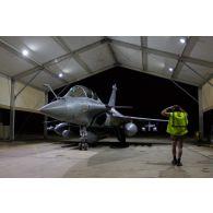 Un mécanicien mène un tour avion autour d'un Rafale au sein d'un hangar de la base aérienne projetée (BAP) en Jordanie.
