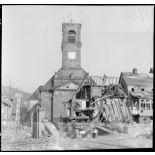 Un camion Dodge WC circule dans le village de Masevaux en ruine. A l'arrière plan, l'église Saint-Martin.