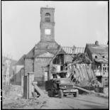 Un camion Dodge WC 62 circule dans le village de Masevaux en ruine. A l'arrière plan, l'église Saint-Martin.