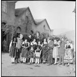 Photographie de groupe de soldats, dont des personnels du SCA (Service cinématographique de l'armée), posant avec de jeunes Alsaciennes à l'occasion de Noël.