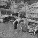 Une femme fait la toilette à son enfant dans la rivière.