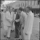 M. Tran Van Huu serre la main d'un civil vietnamien dans une rue d'Hanoï.