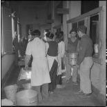 Du personnel vitenamien s'occupe de récipients remplis d'aliments dans un couloir à l'hôpital militaire Lanessan.