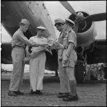 Militaires du rang et officier de l'armée de l'Air regardant un bouquet de fleurs tenu par un marin.