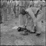 Un officier africain musulman des troupes coloniales se déchausse pour se laver les mains et effectuer ses prières, avant l'embarquement pour le pèlerinage à la Mecque.