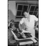 Un soldat, blessé dans la bataille de Diên Biên Phu, est osculté dans la salle de triage de l'hôpital militaire Lanessan.