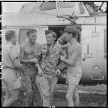 Un infirmier descend d'un hélicoptère sanitaire aidé par ses camarades.