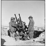 Des artilleurs du 411e RAAA (régiment d'artillerie antiaérienne) servent une mitrailleuse antiaérienne Hochkiss 13,2 mm sur affût bitube.