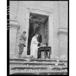 Un aumônier militaire catholique célèbre la messe de Noël à l'intention de tirailleurs marocains et de prisonniers de guerre allemands sur le parvis de l'église d'un village situé à proximité des premières lignes italiennes.