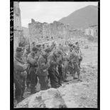 Des tirailleurs du 5e RTM (régiment de tirailleurs marocains) de la 2e DIM (division d'infanterie marocaine) et des prisonniers de guerre allemands et autrichiens se signent au cours d'une messe de Noël, célébrée par un aumônier militaire catholique sur le parvis de l'église d'un village situé à proximité des premières lignes italiennes.