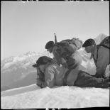 Trois éclaireurs du 199e BCHM allongés ou à genoux dans la neige observent aux jumelles.